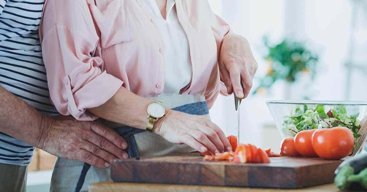 immagine di una coppia affiatata che sta cucinando, a simboleggiare il rapporto tra pomodori e prostata